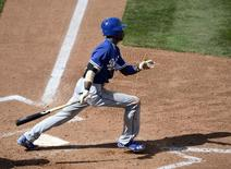 Los Angeles Dodgers second baseman Dee Gordon (9) hits an RBI triple during the fifth inning against the Chicago Cubs at Cubs Park. Mandatory Credit: Christopher Hanewinckel-USA TODAY Sports