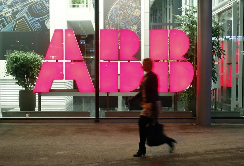 A woman walks past the logo of Swiss industrial group ABB at an office building in Zurich October 24, 2013. REUTERS/Arnd Wiegmann
