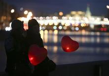 """Люди с воздушными шарами наблюдают проекцию новой работы художника Бэнкси """"Девочка с шаром"""" у здания ЦДХ в Москве 13 марта 2014 года. Наступающий уикенд принесет в столицу России потепление, ожидают синоптики. REUTERS/Sergei Karpukhin"""
