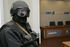 Вооруженный человек в офисе Нафтогаза в Киеве 4 марта 2009 года. Украинская милиция задержала главу правления госкомпании Нафтогаз Евгения Бакулина в рамках расследования коррупции в нефтегазовой отрасли, сообщил министр внутренних дел Арсен Аваков. REUTERS/Konstantin Chernichkin