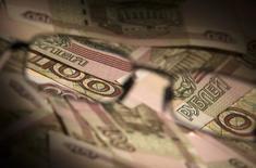 Рублевые купюры в Москве 17 февраля 2014 года. Рубль дорожал в пятницу за счет продаж валюты в преддверии налогов и продолжавшегося сброса излишков длинных валютных позиций, набранных с начала месяца, тем самым игнорируя ухудшение прогнозов суверенного рейтинга РФ и новые западные санкции. REUTERS/Maxim Shemetov