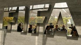 Journalists are reflected in a logo at the FIFA headquarters after a meeting of the executive committee in Zurich October 4, 2013. REUTERS/Arnd Wiegmann