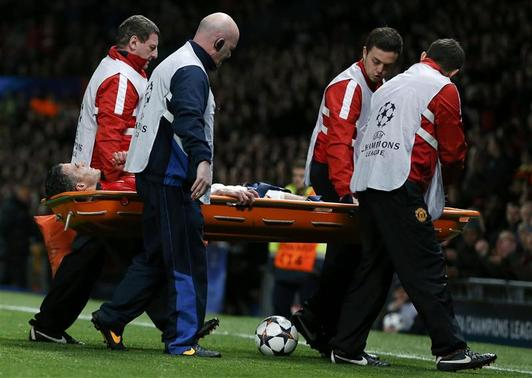 Manchester United's Robin van Persie leaves the pitch on a stretcher during their Champions League soccer match against Olympiakos at Old Trafford in Manchester, northern England, March 19, 2014. REUTERS-Phil Noble