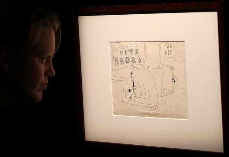 A member of Sotheby's staff looks at an illustration by John Lennon entitled 'Vote Here' at Sotheby's, London March 21, 2014. REUTERS/Paul Hackett