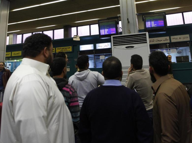 Passengers look at a flight information monitor after the reopening of the airport in Tripoli March 21, 2014. REUTERS/Ismail Zitouny