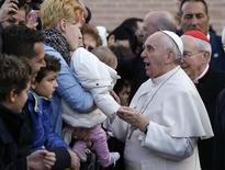 Pope Francis talks with a woman holding a baby as he arrives for his pastoral visit at the Saint Tommaso parish in the outskirts of Rome February 16, 2014. REUTERS/Remo Casilli