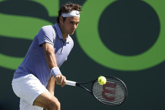 Mar 21, 2014; Miami, FL, USA; Roger Federer hits a backhand against Ivo Karlovic (not pictured) on day five of the Sony Open at Crandon Tennis Center. Federer won 6-4, 7-6. Mandatory Credit: Geoff Burke-USA TODAY Sports - RTR3I3IC