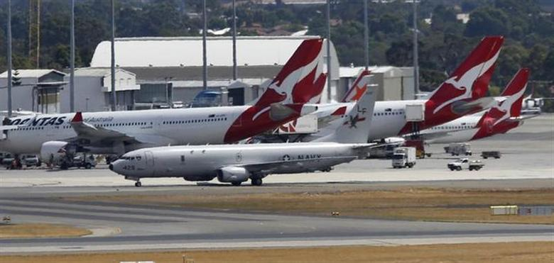 A U.S. Navy P8 Poseidon aircraft taxis past Qantas commercial aircraft before taking off from Perth International Airport, en route to the Indian Ocean March 21, 2014. REUTERS/Jason Reed