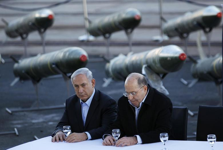 Israel's Prime Minister Benjamin Netanyahu (L) and Defense Minister Moshe Yaalon sit in front of a display of M302 rockets, found aboard the Klos C ship, at a navy base in the Red Sea resort city of Eilat March 10, 2014. REUTERS/Amir Cohen