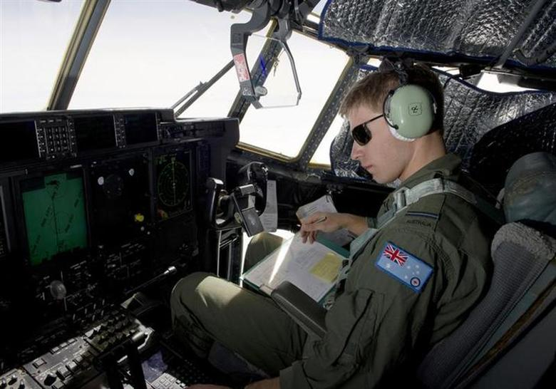 Royal Australian Air Force (RAAF) Pilot Flying Officer Sam Dudman monitors the systems of a RAAF C-130J Hercules aircraft as it prepares to launch two Self Locating Data Marker Buoys in the southern Indian Ocean during the search for missing Malaysian Airlines flight MH370 in this picture released by the Australian Defence Force March 21, 2014. REUTERS/Australian Defence Force/Handout