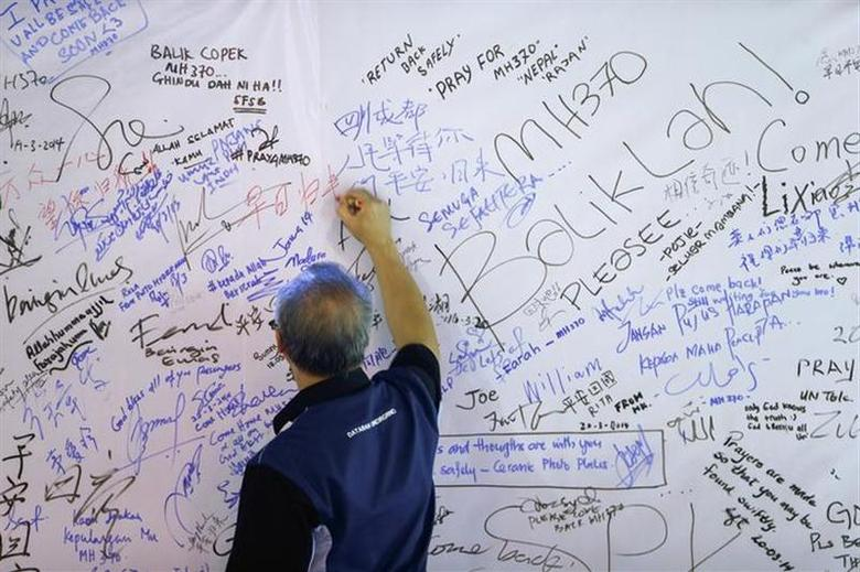 A man writes a message on a board for passengers onboard missing Malaysia Airlines Flight MH370 and their family members, at Dataran Merdeka in Kuala Lumpur March 22, 2014. REUTERS/Samsul Said