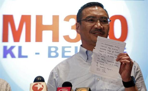 Malaysia's acting Transport Minister Hishammuddin Hussein holds up a note that he has just received on a new lead in the search for the missing Malaysia Airlines Flight MH370, during a news conference at Kuala Lumpur International Airport March 22, 2014. REUTERS/Edgar Su