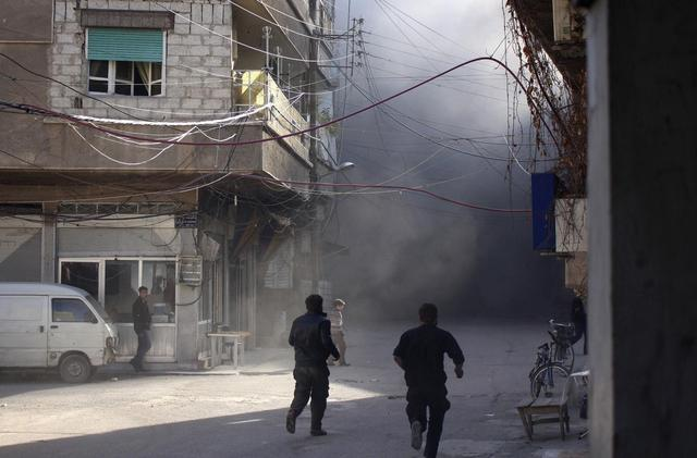 Smoke rises as people run at a site hit by what activists said was shelling by forces loyal to Syria's President Bashar al-Assad in Arbeen, in the eastern Damascus suburb of Ghouta, March 22, 2014. REUTERS/Ammar al-Bushy