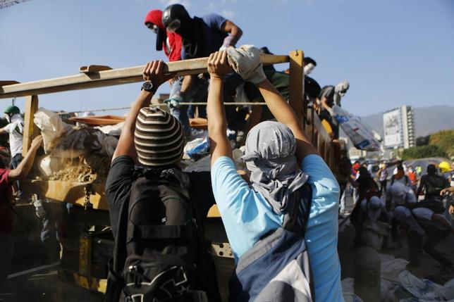 Anti-government protesters unload debris from a truck to build a barricade along a highway during a protest against Nicolas Maduro's government in Caracas March 20, 2014. REUTERS/Marco Bello