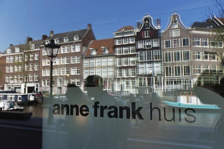 Reflections of tourists and canal houses are seen in the window of the Anne Frank museum in Amsterdam April 24, 2013. REUTERS/Michael Kooren
