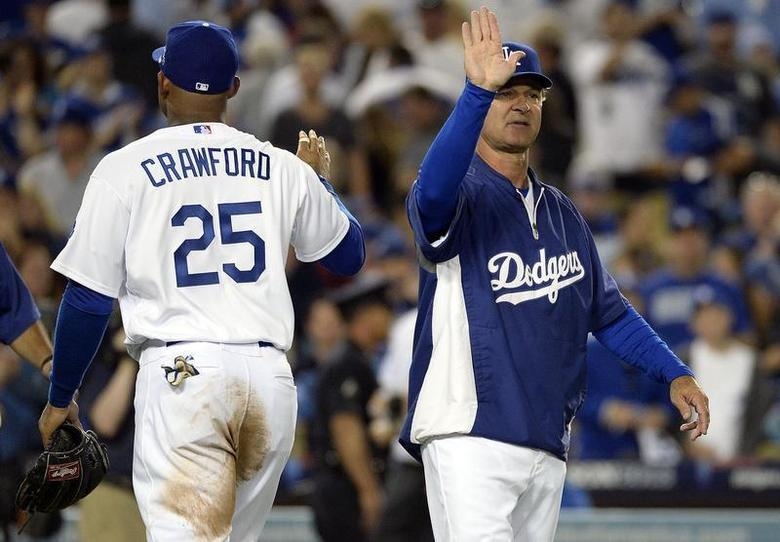 October 14, 2013; Los Angeles, CA, USA; Los Angeles Dodgers left fielder Carl Crawford (25) celebrates with manager Don Mattingly (8) the 3-0 victory against the St. Louis Cardinals following game three of the National League Championship Series baseball game at Dodger Stadium. Richard Mackson-USA TODAY Sports