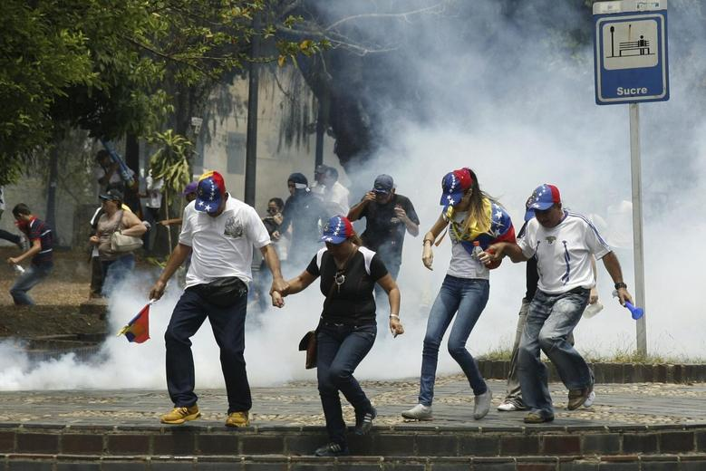 Anti-government protesters run from tear gas during a protest against Nicolas Maduro's government in San Cristobal March 22, 2014. REUTERS/Carlos Eduardo Ramirez