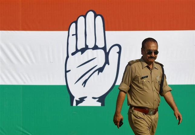 An Indian police officer walks in front of the symbol of India's ruling Congress party during a rally being addressed by Rahul Gandhi, Congress Party vice president and son of Congress chief Sonia Gandhi, ahead of the 2014 general elections at Pratapgarh, in the northern Indian state of Uttar Pradesh March 22, 2014. REUTERS/Jitendra Prakash