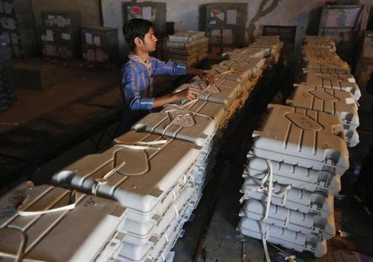 A member of election duty staff arranges electronic voting machines (EVM) inside a strong room ahead of the 2014 general elections in Ahmedabad March 21, 2014. REUTERS/Amit Dave
