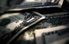 Долларовые купюры в Торонто 26 марта 2008 года. Доллар США удерживает позиции, занятые на прошлой неделе, а курс австралийского доллара упал после публикации слабой производственной статистики Китая. REUTERS/Mark Blinch