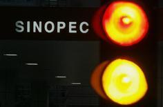 Заправка Sinopec на фоне огней светафора в Гонконге 26 апреля 2010 года. Китайская нефтяная компания China Petroleum and Chemical Corp (Sinopec Corp) планирует сократить расходы в этом году после 35-процентного снижения прибыли в четвертом квартале. REUTERS/Bobby Yip