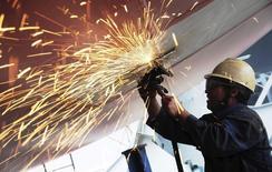 Рабочий полирует днище грузового корабля на верфи в Циндао 1 июля 2013 года. Активность в промышленном производстве Китая сократилось в первом квартале 2014 года, свидетельствуют предварительные результаты частного исследования. REUTERS/China Daily