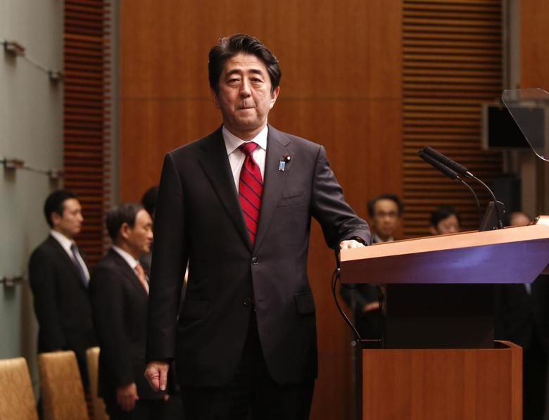 Japan's Prime Minister Shinzo Abe poses for photos as he attends a news conference at his official residence in Tokyo March 20, 2014, after Japan's parliament enacts a budget for fiscal 2014. Abe said on Thursday he hopes to resume formal talks with North Korea as soon as possible. REUTERS/Yuya Shino