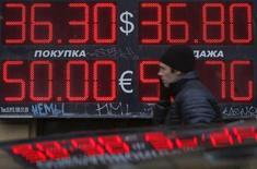 Мужчина проходит мимо пункта обмена валюты в Москве 3 марта 2014 года. Рубль торгуется в плюсе недалеко от границы смены интервенций Центробанка, выступающей сопротивлением укреплению российской валюты, поддержкой же рублю выступает продажа экспортной выручки перед крупными налогами. REUTERS/Maxim Shemetov