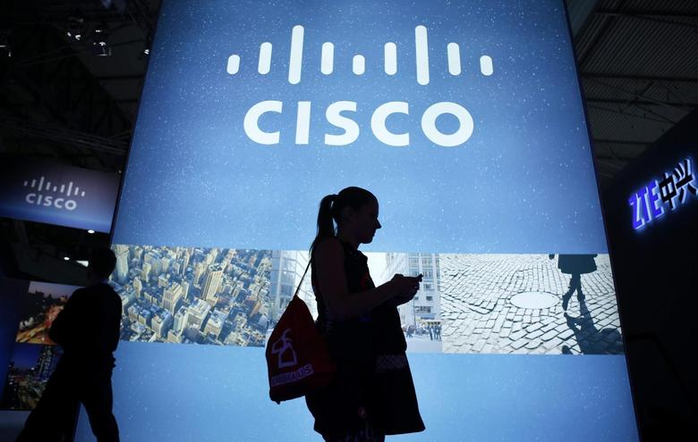 A visitor walks past a Cisco advertising panel as she looks at her mobile phone at the Mobile World Congress in Barcelona February 27, 2014. REUTERS/Albert Gea