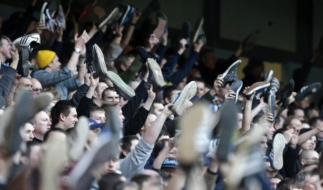 Leeds United supporters wave their shoes in the air as they sing during their FA Cup fifth round soccer match against Manchester City at The Etihad Stadium in Manchester, northern England, February 17, 2013. REUTERS/Phil Noble