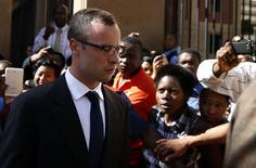 Olympic and Paralympic track star Oscar Pistorius (L) leaves after his trial for the murder of his girlfriend Reeva Steenkamp, at the North Gauteng High Court in Pretoria, March 24, 2014. REUTERS/Siphiwe Sibeko