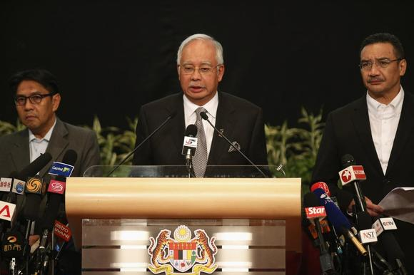 Malaysia's Prime Minister Najib Razak (C) makes an announcement on the latest development on the missing Malaysia Airlines MH370 plane at Putra World Trade Center in Kuala Lumpur March 24, 2014. REUTERS/Edgar Su