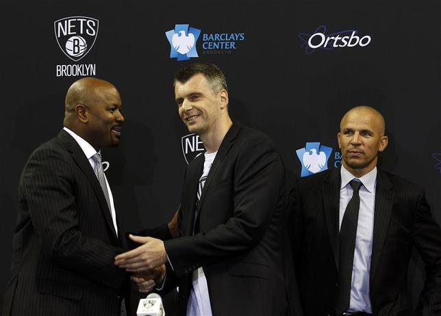 NBA Brooklyn Net's principal owner Mikhail Prokhorov (C) shakes hands with general manager Billy King in front of head coach Jason Kidd (R) after a news conference in Brooklyn, New York July 18, 2013. REUTERS/Adam Hunger