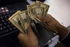 Um caixa conta dólares em Nova York. Com a balança comercial cada vez mais fraca, o Brasil terá déficit em transações correntes ainda maior neste ano, após fechar fevereiro com rombo recorde, sem que os investimentos produtivos sejam suficientes para financiá-lo. 28/11/2013 REUTERS/Eric Thayer
