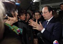 O presidente francês François Hollande fala com parteiras após votar no primeiro turno das eleições locais francesas, em Tulle. Hollande deve manter as reformas econômicas planejadas com corte nos gastos apesar de ter sido punido nas eleições locais, onde a Frente Nacional (FN) anti-imigração obteve ganhos, informou o ministro das Finanças francês, na segunda-feira. 23/03/2014 REUTERS/Regis Duvignau