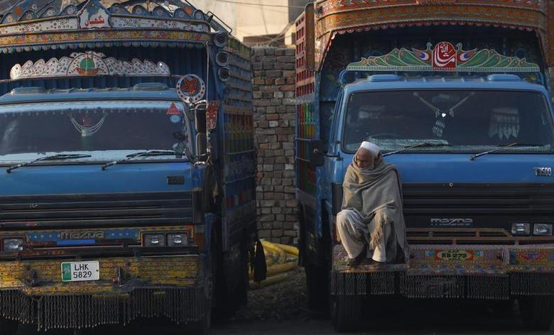 A man sits on the front of a truck while wearing woollen shawl to keep himself warm in the cold at a whole sale market in Rawalpindi December 27, 2013. REUTERS/Mian Khursheed