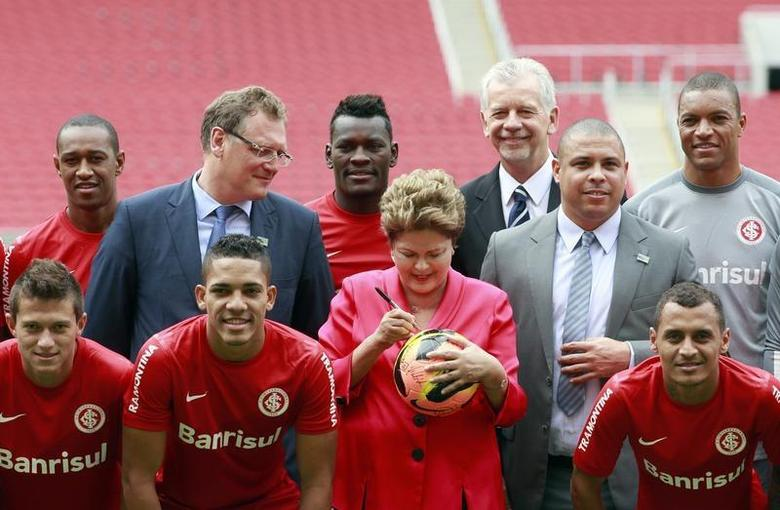 Brazil's President Dilma Rousseff (C) signs a soccer ball as she poses for a picture with FIFA Secretary General Jerome Valcke (3rd L), former Brazilian soccer player and member of the 2014 World Cup local organizing committee Ronaldo (3rd R), Porto Alegre's Mayor Jose Fortunati (center R) and Brazil's Internacional soccer club players during the opening ceremony of the Beira-Rio stadium, which will be one of the stadiums hosting the 2014 World Cup soccer matches, in Porto Alegre February 20, 2014. REUTERS/Edison Vara