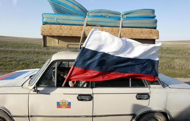 A car drives with a Russian flag on a road outside the Crimean port city of Feodosia March 24, 2014. REUTERS/Shamil Zhumatov
