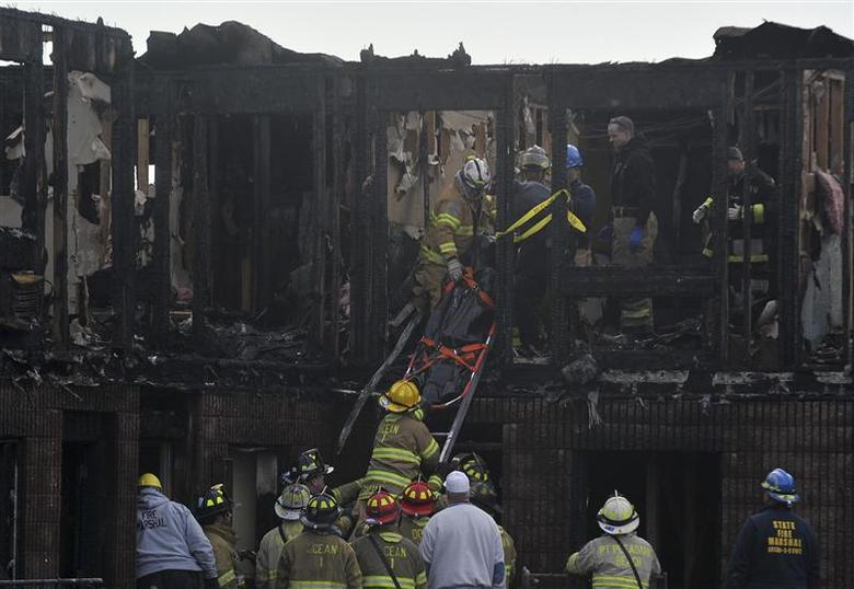 Rescue workers remove a body found in the charred remains of the Mariner's Cove Inn in Point Pleasant Beach, New Jersey, March 21, 2014. REUTERS/Charles Mostoller