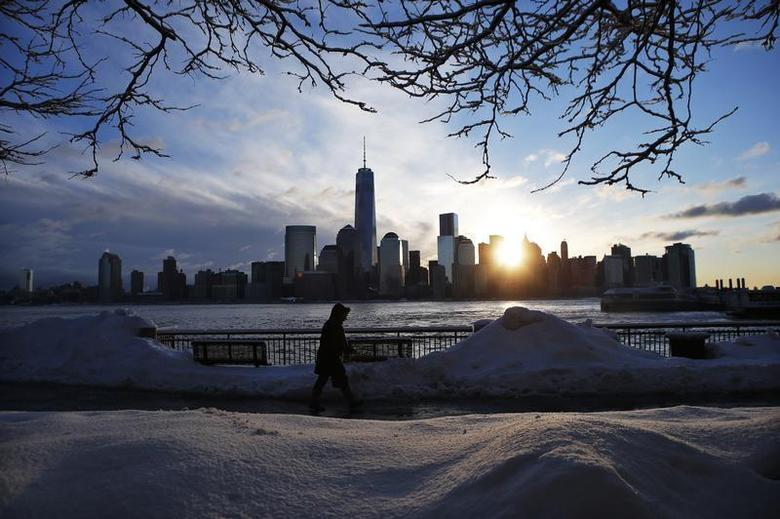 The New York skyline and the One World Trade Center are seen in the distance as a man makes his commute after a night of snow from New York City to Exchange Place in New Jersey, February 14, 2014. REUTERS/Eduardo Munoz