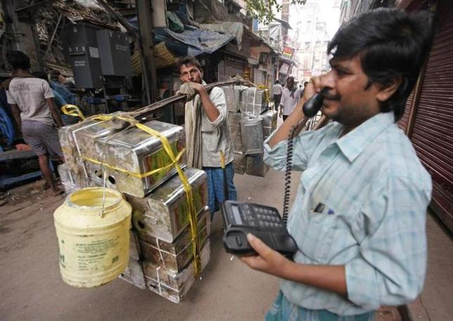 A labourer carries oil containers as a man speaks on a wireless phone outside the Public Call Office (PCO) at a wholesale grocery market in Kolkata December 8, 2010. REUTERS/Rupak De Chowdhuri/Files