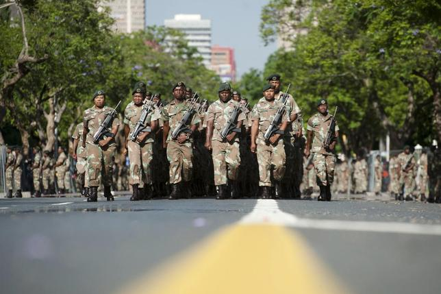 South African National Defence Force (SANDF) soldiers parade on the streets near the Union Buildings, where the body of former South African President Nelson Mandela will lie in state, in Pretoria December 12, 2013. REUTERS/Ihsaan Haffejee