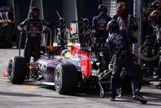 Red Bull Formula One driver Sebastian Vettel of Germany is assisted by his pit crew as he retires from the Australian F1 Grand Prix at the Albert Park circuit in Melbourne March 16, 2014. REUTERS/David Gray