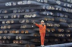 Un trabajador junto a una serie de barras de acero en Qingdao, China, mar 17 2014. China ha dejado de lado una antigua meta para que las 10 principales siderúrgicas controlen el 60 por ciento del sector a partir del 2015, una meta que ha sido criticada por compañías como Baosteel por causar una aumento de capacidad que no es rentable. REUTERS/China Daily