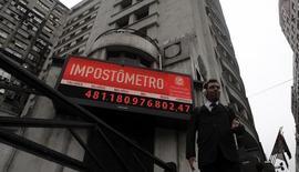 Um homem passa na frente do Impostômetro, que exibe a soma paga em impostos por cidadãos brasileiros, no centro de São Paulo. O governo prepara o anúncio de aumento de impostos de alguns setores para gerar arrecadação extraordinária de cerca de 4 bilhões de reais este ano e ajudar o Tesouro Nacional a aumentar os repasses para a Conta de Desenvolvimento Energético (CDE). 27/04/2012 REUTERS/Nacho Doce