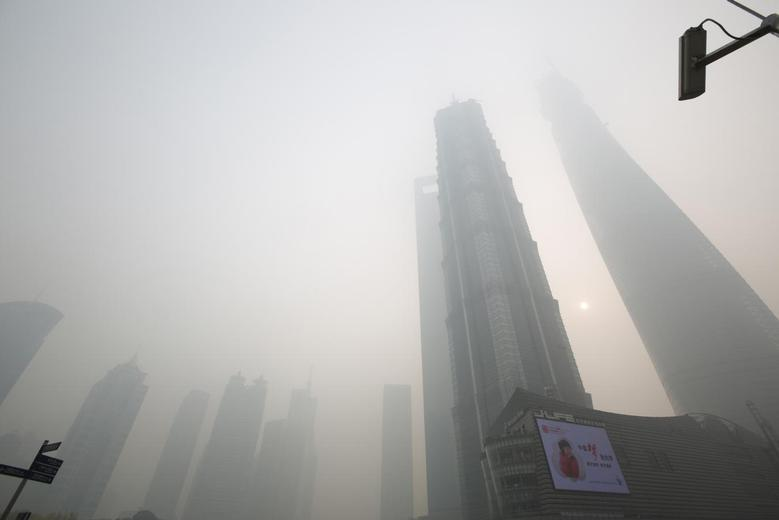An electronic screen and buildings are seen amid heavy smog at the financial district of Pudong in Shanghai December 6, 2013. REUTERS/Aly Song