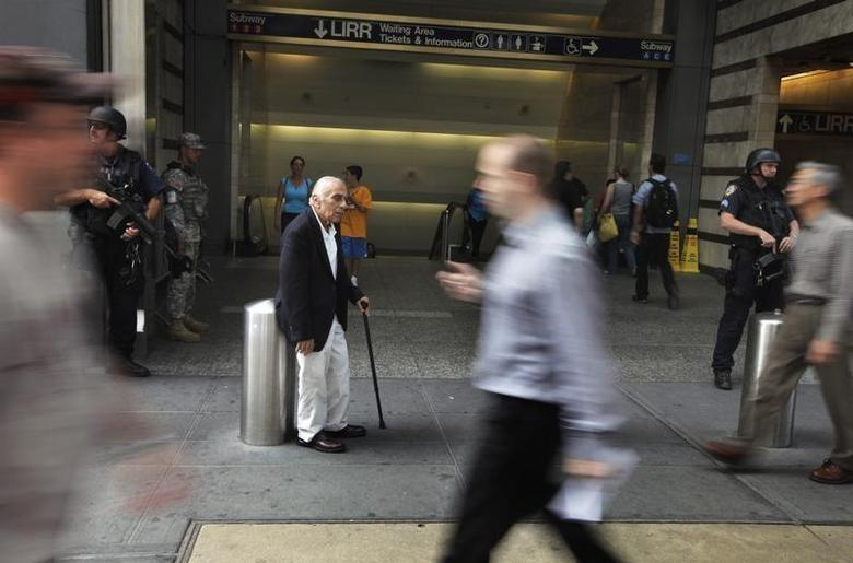 A man pauses to relax as members of the public walk past heavily armed members of a New York Police Department Hercules team in outside of Penn Station in New York August 24, 2011. REUTERS/Lucas Jackson