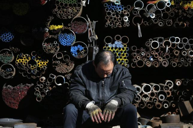 A worker takes a nap in front of steel products stacked at a steelworks in Seoul January 28, 2014. REUTERS/Kim Hong-Ji