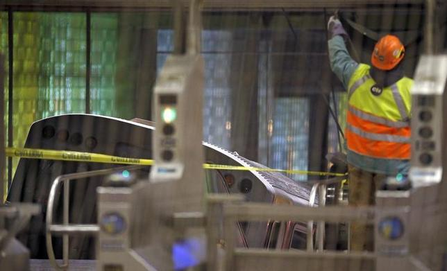 A worker puts up a tarp to cover the scene where a Chicago Transit Authority subway train crashed into a platform at O'Hare International Airport in Chicago March 24, 2014. REUTERS/Jim Young