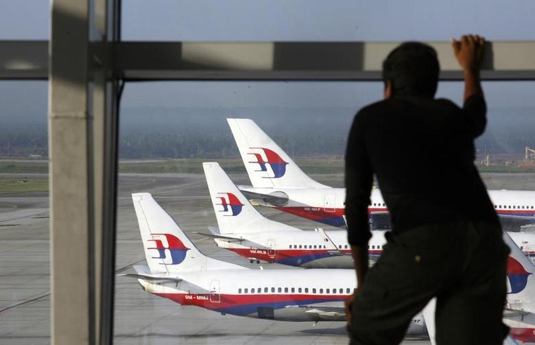 A traveller stands at the viewing gallery overlooking Malaysian Airline System (MAS) aircrafts at Kuala Lumpur International Airport in Sepang outside Kuala Lumpur December 23, 2009. REUTERS/Bazuki Muhammad